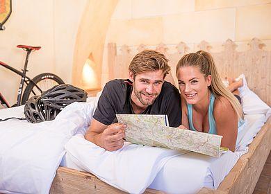 Fahrradfahrer, Fahrrad, Tour planen im Bett des Hotel Arthus, Fahrradkarte, Paarurlaub
