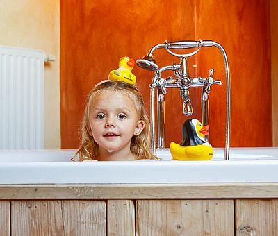 Kinder im Hotel Arthus, Badespaß, Freistehende Badewanne im Holzzuber, kleines Burgfräulein, Quietscheentchen, Quietscheente