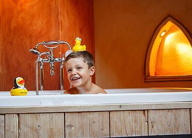 Kinder im Hotel Arthus, Badespaß, Freistehende Badewanne im Holzzuber, kleiner Ritter, Quietscheentchen, Quietscheente